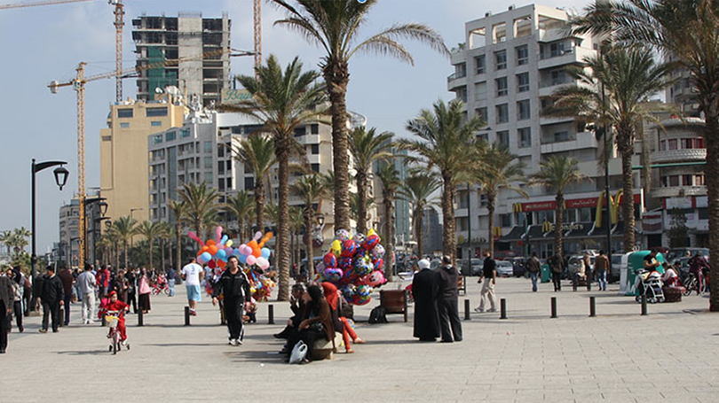 People walk on a boardwalk in the Middle East.
