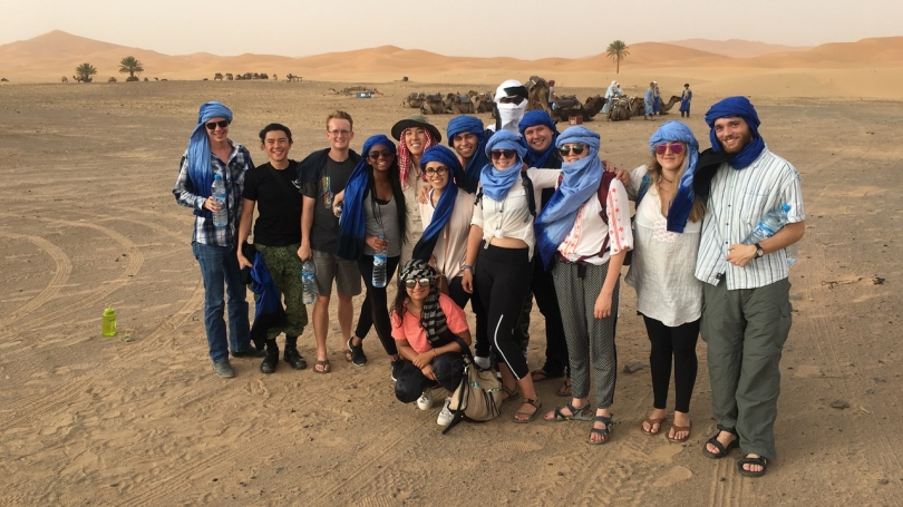 Students pose in front of camels in the desert.